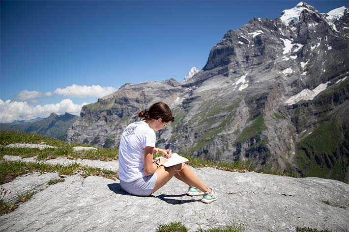 Student journaling in the Swiss Alps